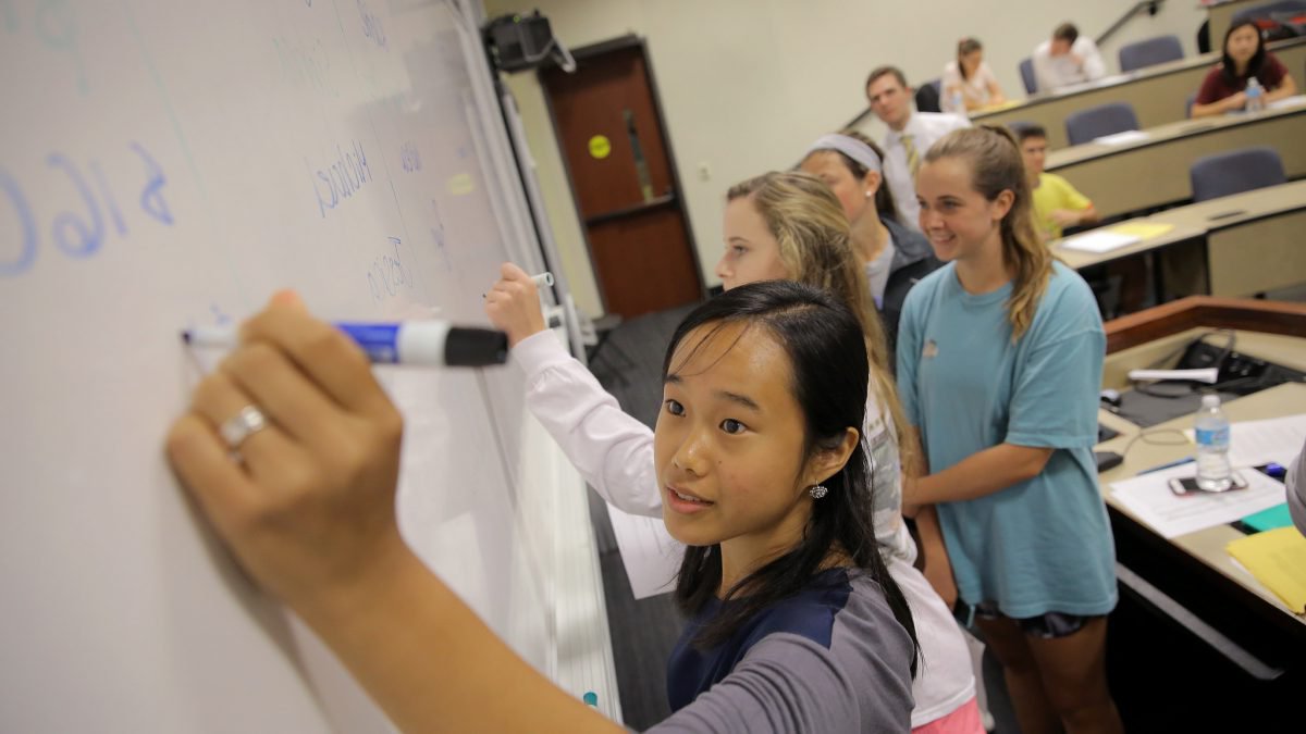 Students writing on a whiteboard.