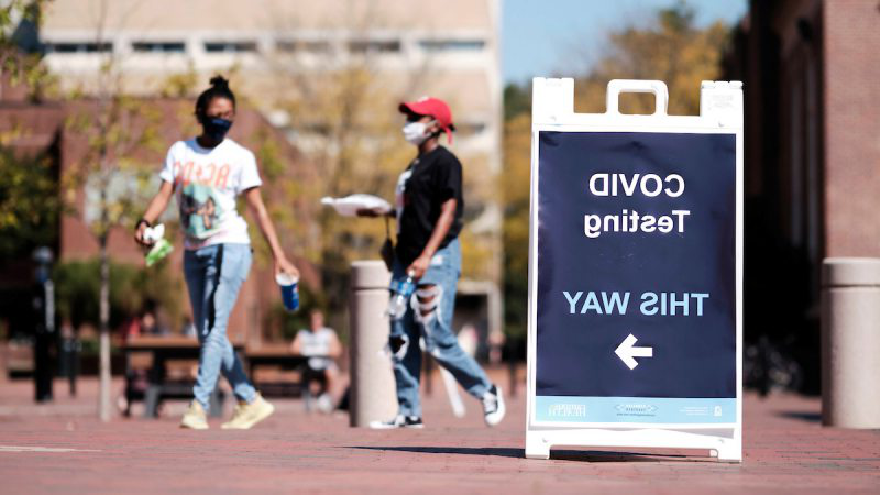 Students walk on campus near a sign that reads