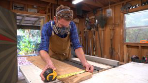 A woodworker measures a piece of wood.